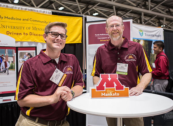 Two male physicians wear maroon and gold University of Minnesota Family Medicine Residency polo shirts.