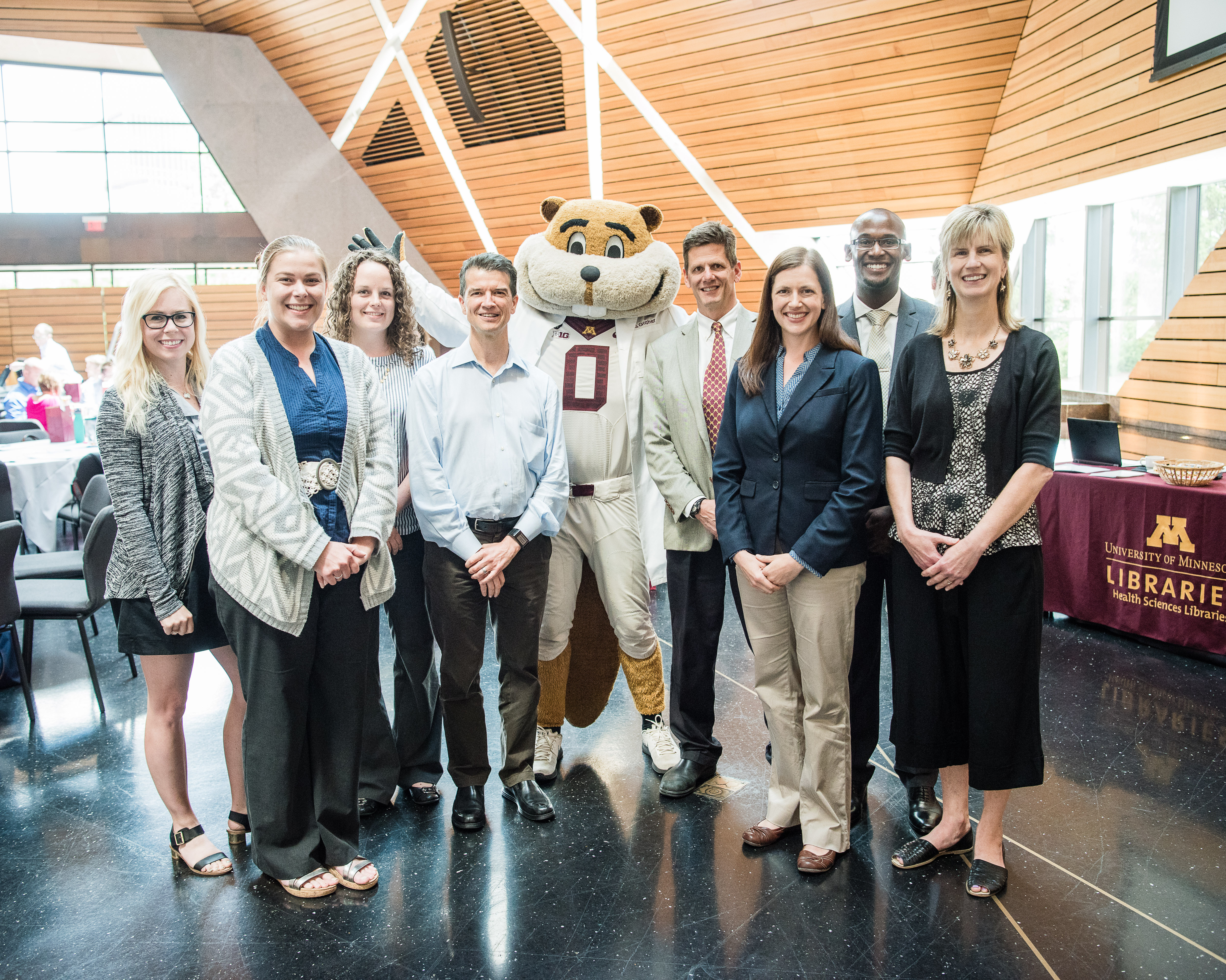 8 people in office attire standing posed with Goldy Gopher